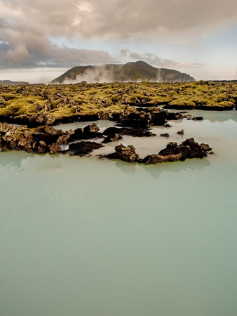 grindavik: Silica rich blue green water outside of the Blue Lagoon Spa in a lava rock green mossy field in Iceland. Stock Photo