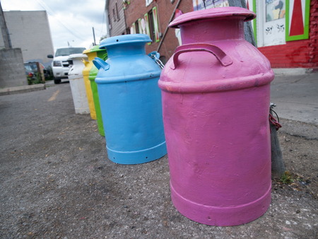 milk jugs: Line of colourful painted milk jugs on the street in Toronto, Ontario, Canada. Stock Photo