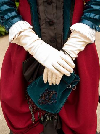 velvet dress: Close up of white gloves and green velvet purse and red victorian velvet dress.