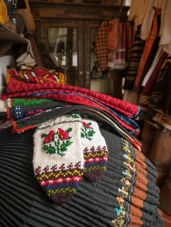 pleated: Traditional Bulgarian knit slippers and pleated skirt at antique store in Bulgaria, Europe.
