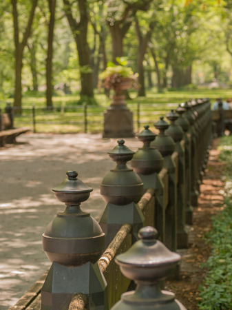 paved: Green metal fence posts and paved pathway at central park in Manhattan, New York City, USA.