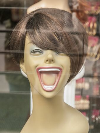 fake smile: Laughing mannequin with brown wig short hair and pink lipstick in store front window,
