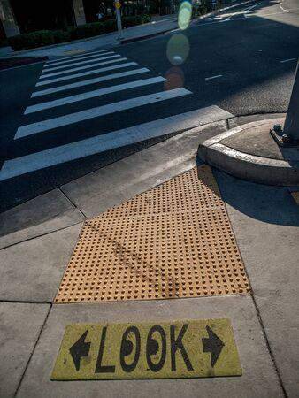 cross walk: Sign on sidewalk that says LOOK with cartoon eyes in the Os and two arrows in front of cross walk in Hollywood, Los Angeles, California, USA.