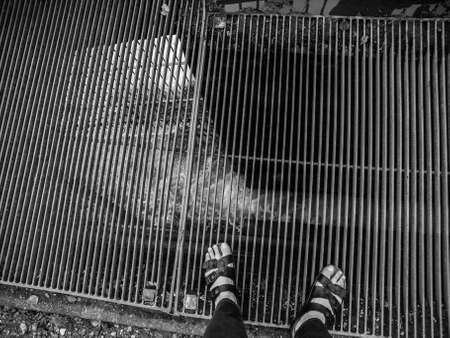 rushing water: Looking down at feet in black leather sandals standing on grate over rushing water. Stock Photo