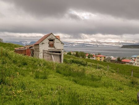 broken down: Old broken down house on a green hillside looking over the water in Isafjordur Iceland. Stock Photo