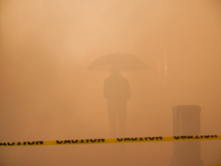 caution tape: Yellow caution tape, fog and silhouette of man holding umbrella at night.