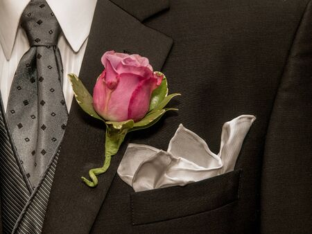 lapel: Pink and green rose on lapel of black suit jacket.