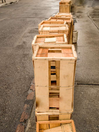 kensington: Empty wood crates piled on top of each other lining the sidewalk, pavement is wet in Kensington Market, Toronto, Ontario, Canada. Stock Photo