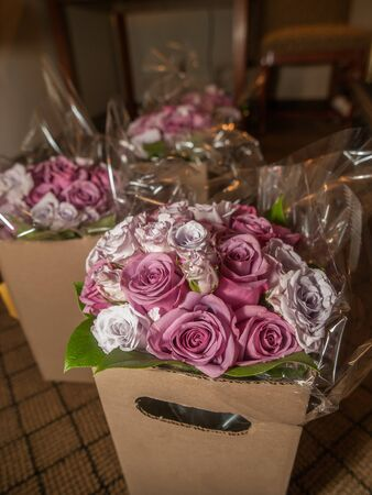 short order: Three boxes of pink and purple roses for table centerpieces.