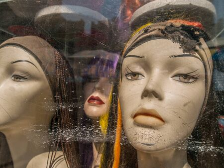 bitchy: Three female caucasian mannequin heads wearing scarves with very serious expressions in a scratched up store front window in Manhattan, New York City, USA.