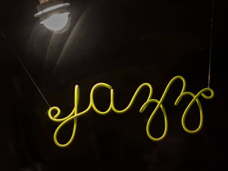 cursive: Green cursive jazz sign and light in store front window. Stock Photo