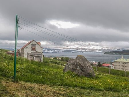 broken down: Old broken down house and a green clothesline on a green hillside looking over the water in Isafjordur Iceland.  on a green hillside looking over the water in Isafjordur Iceland.