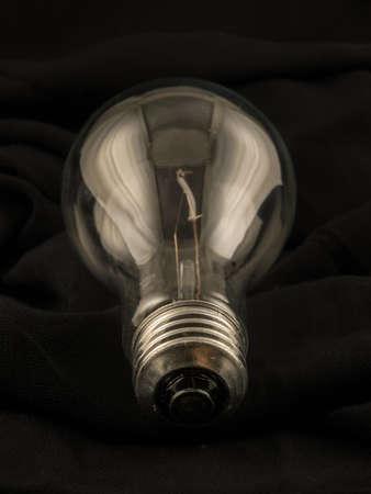 unlit: Unlit light bulb on black cloth.
