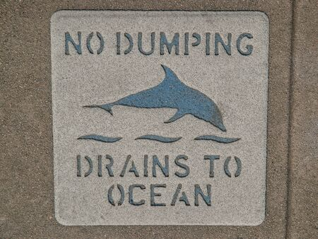 dumping: Sign on sidewalk that says No Dumping Drains to Ocean with a picture of a dolphin in Los Angeles California. Stock Photo