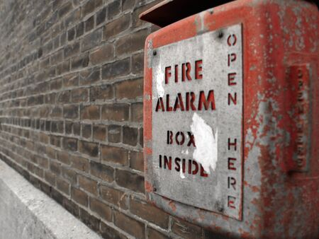 fire rescue: Old red fire alarm box with peeling paint on outdoors on a brick wall