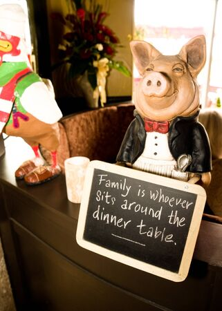 dinner jacket: Figurine of a pig dressed as a maitred with a black jacket and red bowtie and apron in front of a chalkboard sign that says Family is whoever sits around the dinner table.