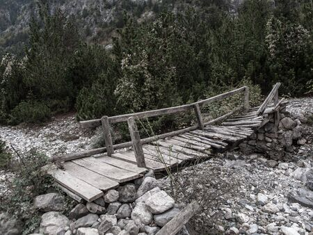 rickety: Collapsing wooden bridge over rocks in Theth, Albania, Europe.