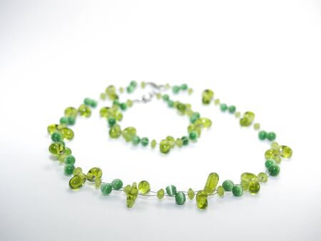 jewellry: Matching glass beaded green necklace and bracelet on a white background. Stock Photo