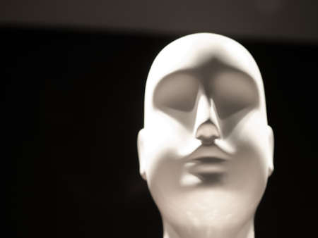 mannequin head: White ceramic bald androgynous mannequin head against black background in retail storefront window. Stock Photo