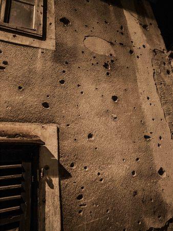 gunfire: Gun shot holes on a gray concrete building in Sarajevo, Bosnia and Herzegovina, Europe.