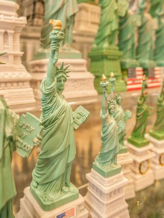 souvenirs: Many Statue of Liberty souvenirs lined up on a store shelf in New York City, USA.