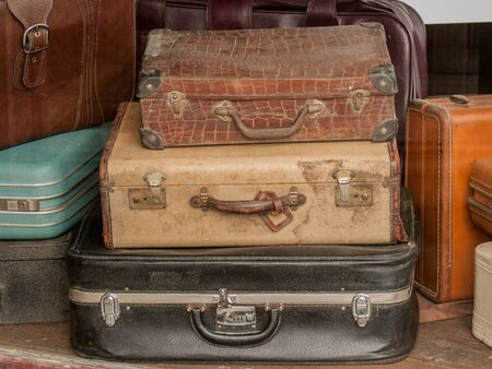 thrift: Stack of old dirty vintage suitcases in a Thrift Store window.