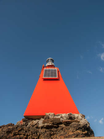 triangle shaped: Bright red orange small triangle shaped lighthouse at the top of the boardwalk hike on Bartolome, Galapagos Islands, Ecuador. Stock Photo