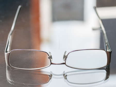 scratched: Pair of upside down Versace metal frame glasses on a glass table with reflections.
