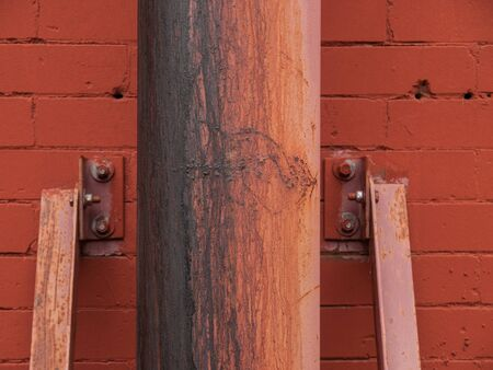 metal post: Rusted metal post against painted red brick wall in downtown Montreal, Quebec, Canada.