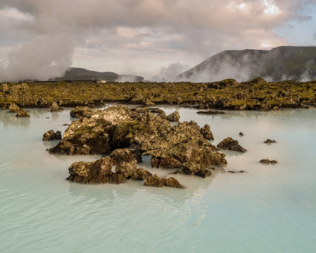hot rock therapy: Silica rich blue green water outside of the Blue Lagoon Spa in a lava rock green mossy field in Iceland. Stock Photo