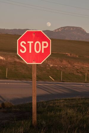 highway sign: Stop sign along the Pacific Coast Highway at sunset in front of a full moon in California. Stock Photo