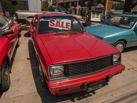 Coche viejo portón rojo para la venta en un lote de autos usados ??en Toronto, Ontario, Canadá. Foto de archivo - 52056352
