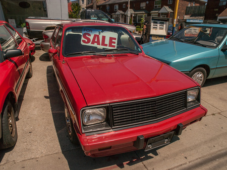 Old red hatchback car for sale in a used car lot in Toronto Ontario, Canada.