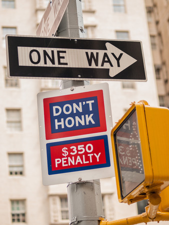 honk: Black and white One Way sign and blue and red Dont Honk 350 Penalty sign at a crosswalk on a post in Manhattan, New York City, USA.