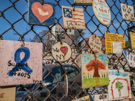 Ceramic tiles with messages about September 11th, 911 attacks in New York City hang from a fence in Greenwich Village, New York, USA.