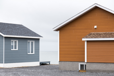 Blue and orange wood sided cabins on the St Lawrence River in Matane Quebec. The cabins are surrounded by gravel and the sky is overcast.
