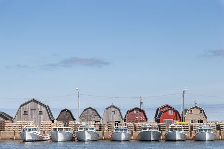 sheds: A line of fishing sheds and tied up fishing boats at Malpeque Harbour in Prince Edward Island PEI on the east coast of Canada.