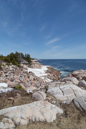 wisps: Large boulders and rocks half covered in snow overlooking the Atlantic Ocean in spring on the Cabot Trail in Nova Scotia, east coast Canada. The sky is clear blue with wisps of cloud. Stock Photo