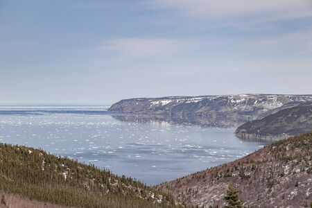float cloud: View overlooking the Atlantic Ocean in spring on the Cabot Trail in Nova Scotia, east coast Canada. Chunks of ice float in the water. The sky is mostly blue with wisps of cloud. Stock Photo