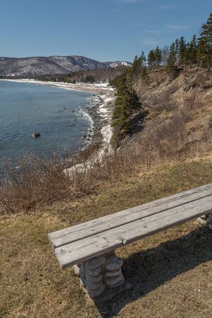 shore line: A wooden bench overlooking the Atlantic Ocean in spring on the Cabot Trail in Nova Scotia, east coast Canada. Patches of snow cover some of the shore line.
