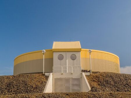grindavik: Circular industrial yellow and gray building on top of gravel platform against a blue clear sky near Keflavik Iceland.