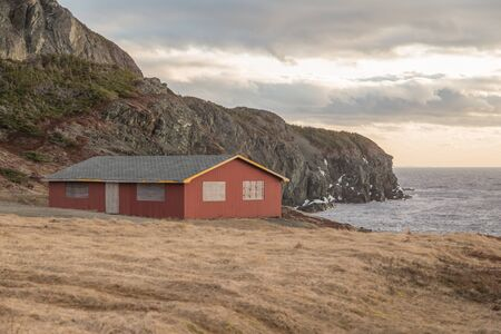Red wood building with boarded up windows on the seaside in Twillingate, Newfoundland, Canada at sunset. Yellow grass in the forefront.