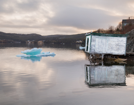 Large chunk of ice and a rustic boathouse on black water on a cloudy day at sunset in Trinity, Newfoundland, Canada. Stock Photo