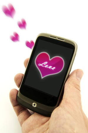 Hand holding phone with valentine love message. Pink hearts are flying from display Stock Photo - 11879111