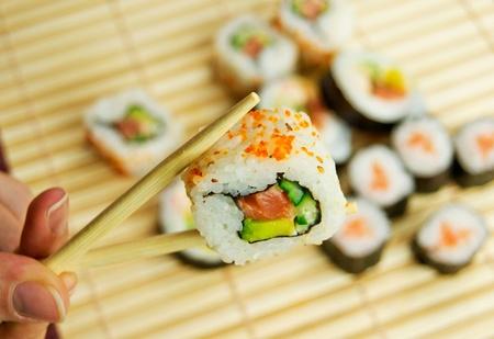 japanese sake: Mano que sostiene el sushi. Comida tradicional japonesa. Servilleta de bambú en el fondo