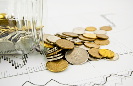Coins Spilled From Jar on business background photo