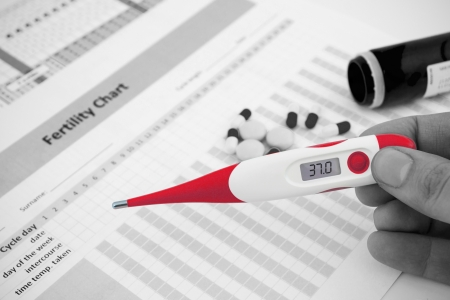 progesterone: Red thermometer on black and white fertility composition
