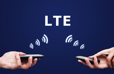 LTE high speed mobile internet connection. Hand holding cell with streaming data photo