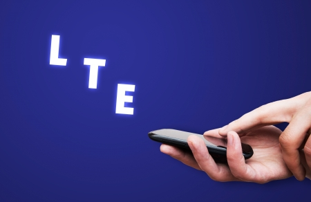wariety: LTE high speed mobile internet connection. Hand holding cell with streaming data