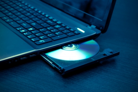 rom: Laptop with open CD - DVD drive. Abstract light composition Stock Photo
